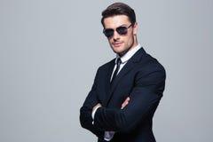 Uomo d'affari in occhiali da sole che stanno con le armi piegate Immagini Stock