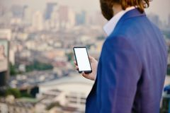 Uomo d'affari occidentale facendo uso di uno smartphone con l'isolato dello schermo in bianco immagine stock