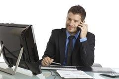 Uomo d'affari occupato allo scrittorio facendo uso del telefono cellulare Immagine Stock Libera da Diritti