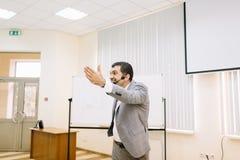 Uomo d'affari occupato che parla su una conferenza su un fondo vago Concetto di motivazione Copi lo spazio Fotografia Stock