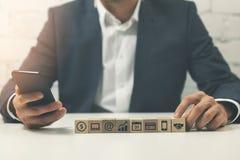 uomo d'affari occupato che per mezzo dello smartphone all'elaborazione multitask dell'ufficio immagine stock