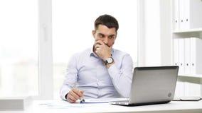 Uomo d'affari occupato con il computer portatile e le carte in ufficio archivi video