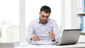 Uomo d'affari occupato con il computer portatile e le carte in ufficio video d archivio