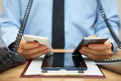 Uomo d'affari occupato in ufficio allo scrittorio facendo uso di due telefoni cellulari, Immagine Stock