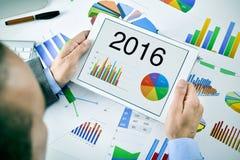 Uomo d'affari osservando una previsione economica per il 2016 nel suo Fotografia Stock
