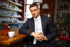 Uomo d'affari in panni convenzionali che beve caffè fotografie stock
