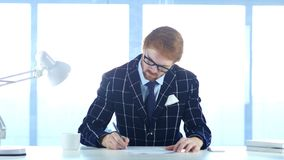 Uomo d'affari Paperwork della testarossa, scrittura e funzionamento sul computer portatile immagini stock libere da diritti