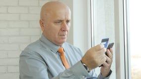 Uomo d'affari Paying Online Shopping con la carta di credito facendo uso di Smartphone fotografie stock libere da diritti