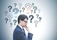 Uomo d'affari pensieroso in vetri, punti interrogativi immagini stock libere da diritti