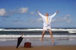 Uomo d'affari pensionato che salta con la felicità su una bella spiaggia tropicale, concetto di libertà di pensionamento Fotografie Stock