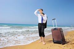 Uomo d'affari perso con i suoi bagagli che cercano il modo su una spiaggia Immagine Stock