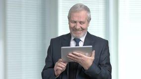 Uomo d'affari più anziano felice facendo uso della compressa del pc video d archivio