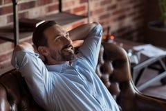 Uomo d'affari positivo allegro che prende piacere nel suo rilassamento Fotografia Stock