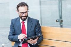 Uomo d'affari positivo astuto che per mezzo di una compressa mentre sedendosi sul banco immagini stock