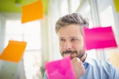 Uomo d'affari premuroso che esamina le note adesive Immagine Stock