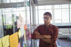 Uomo d'affari premuroso che esamina le note adesive in ufficio Fotografia Stock Libera da Diritti