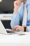 Uomo d'affari premuroso che lavora ad un computer portatile Fotografia Stock Libera da Diritti