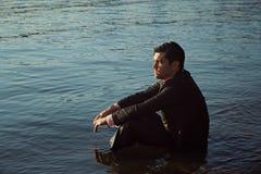 Uomo d'affari premuroso messo su una riva del lago fotografia stock