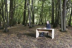 Uomo d'affari premuroso Sitting At Desk in foresta fotografia stock libera da diritti