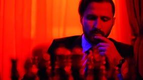Uomo d'affari premuroso in un vestito che si siede su un fondo vago che pondera strategia che gioca scacchi stock footage