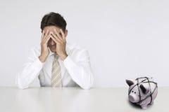 Uomo d'affari preoccupato alla tavola con il porcellino salvadanaio bloccato che rappresenta le difficoltà finanziarie fotografia stock