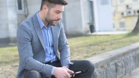 Uomo d'affari preoccupato con uno smartphone archivi video
