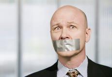 Uomo d'affari preoccupato messo la museruola a con nastro adesivo del condotto Immagine Stock Libera da Diritti