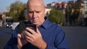 Uomo d'affari preoccupato Text Using Cellphone che cammina sulla via video d archivio