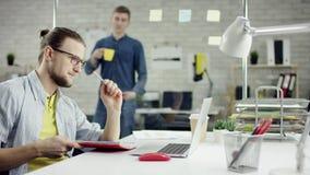 Uomo d'affari produttivo che pende il lavoro d'ufficio indietro di finitura sul computer portatile, efficace responsabile soddisf video d archivio