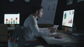 Uomo d'affari professionale che analizza i grafici ed i dati finanziari nell'ufficio di notte stock footage