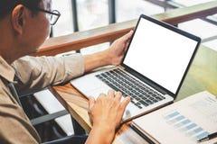 Uomo d'affari professionale senior nell'abbigliamento casual che lavora facendo uso del computer portatile in caffè con funzionam immagini stock