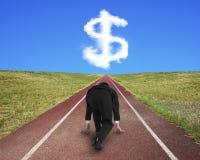 Uomo d'affari pronto a correre sulla pista corrente verso il simbolo di dollaro Fotografia Stock