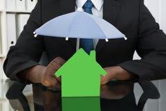 Uomo d'affari Protecting House Model con l'ombrello Fotografia Stock Libera da Diritti