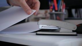 Uomo d'affari Putting Contracts Pages insieme facendo uso di uno strumento metallico dell'ufficio fotografia stock