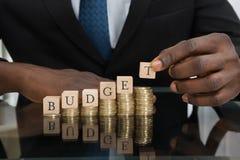 Uomo d'affari Putting The Letters del bilancio di parola sulle monete Fotografia Stock