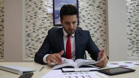 Uomo d'affari Reading Documents con i grafici archivi video