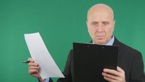 Uomo d'affari Reading Documents e contratti con lo schermo verde nel fondo fotografia stock