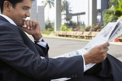 Uomo d'affari Reading Newspaper Outdoors Immagini Stock
