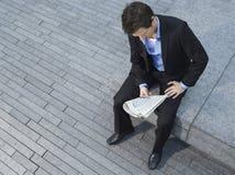 Uomo d'affari Reading Newspaper Outdoors Fotografie Stock Libere da Diritti