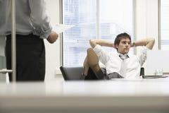 Uomo d'affari Reclining On Chair e capo di trascuratezza Fotografia Stock
