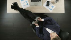 Uomo d'affari ricco rilassato che conta soldi, sedentesi con i piedi sulla tavola, vista superiore stock footage