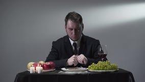 Uomo d'affari ricco in un vestito che eatting o che assaggia un pezzo di carne accanto alle mele, all'uva e ad un vetro di vino r archivi video
