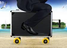 Uomo d'affari Ride sulla valigia alla spiaggia Fotografia Stock
