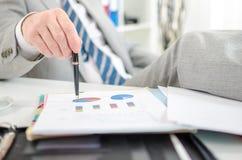 Uomo d'affari rilassato che controlla i grafici finanziari Fotografie Stock