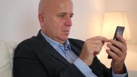 Uomo d'affari rilassato nelle notizie finanziarie leggenti del cellulare di uso dell'ufficio su Internet stock footage