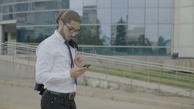 Uomo d'affari in rivestimento della tenuta del vestito sopra la sua spalla ed esaminare il suo smartphone mentre aspettando il dr video d archivio