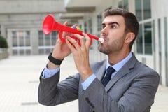 Uomo d'affari rumoroso che gioca una tromba di plastica immagine stock