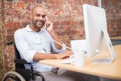 Uomo d'affari in sedia a rotelle che funziona al suo scrittorio sul telefono Immagini Stock
