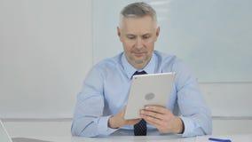 Uomo d'affari senior Browsing Internet sulla compressa in ufficio stock footage