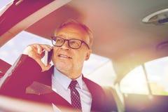 Uomo d'affari senior che rivolge allo smartphone in automobile Immagini Stock